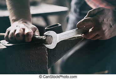 Man working with wrench and old steel element