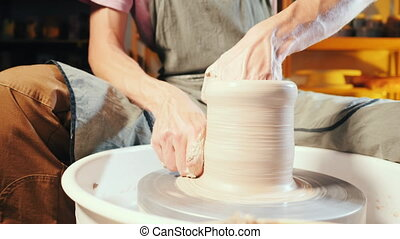Man works his hands with clay. Process of creating product...
