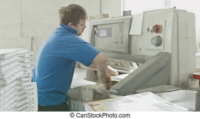 Man works on cutter guillotine machine in a printing factory