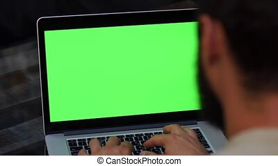 Man works on the laptop with green screen.