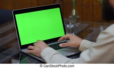 Man works on the laptop with green screen