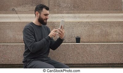 Man works on the tablet sitting on footsteps
