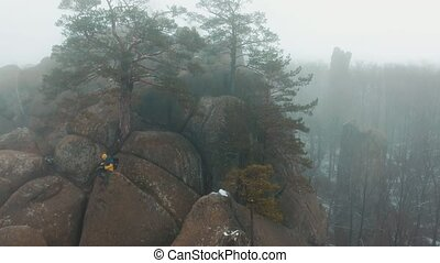 Man works with a smartphone sitting on the top of the mountain covered with fog
