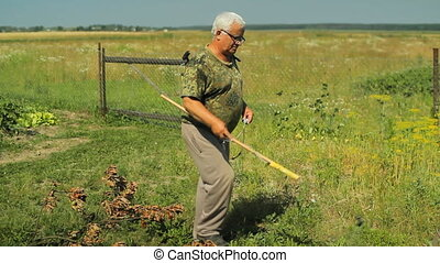 Man works with garden spray in the field near home