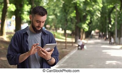 Man works with tablet standing in the park