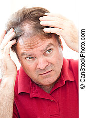 Man Worried About Balding - Man in his forties looking in...
