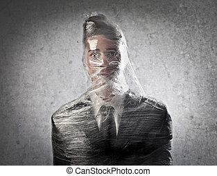 man wrapped in cellophane on gray background