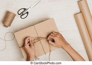 Man wrapping gift. A parcel wrapped in brown paper and tied...