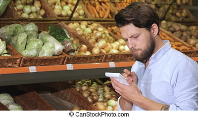 Man write in his notebook at the supermarket