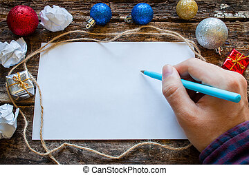 man writes a list of gifts for the new year
