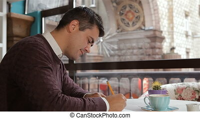 Man writes in his notebook at the cafe