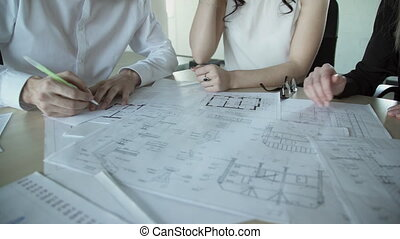 Man writes on a paper plan, and two women are helping with paperwork.