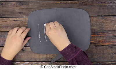 Man writes the word IDEA with chalk on a chalkboard, stylized as a thought.