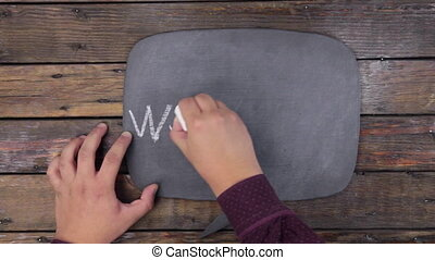 Man writes the word WORKSHOP with chalk on a chalkboard,...