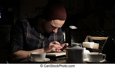 Man writing a to do list in a bar at evening