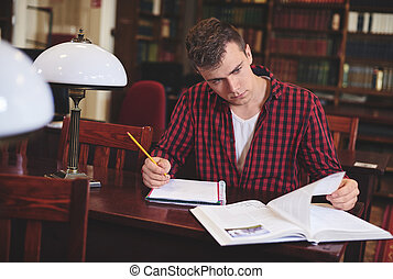 Man writing at desk in library