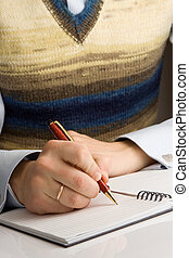 man writing by pen on notebook