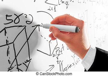 Man writing complex math formulas on whiteboard
