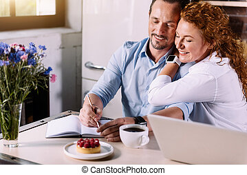 Man writing in notebook near his wife