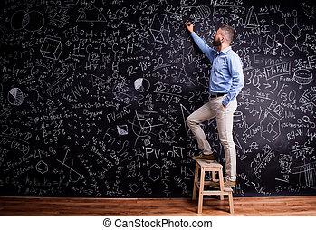 Man writing on big blackboard with mathematical symbols -...