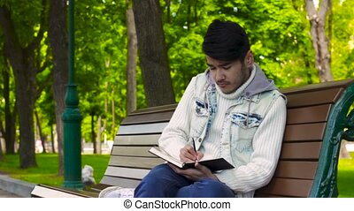 Man writing something in notebook sitting in the park