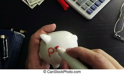 Man writing word pension on a side of piggy bank. Retirement concept.