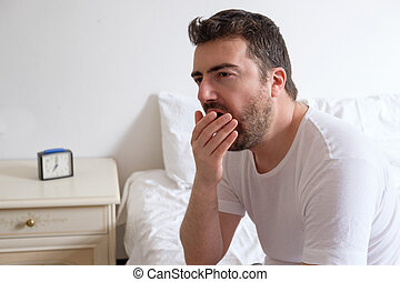 Man yawning. He is sitting on the edge of a bed in the morning