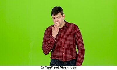 Man yawns, he is sleepy and wants to go to bed. Green screen
