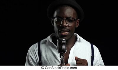 Man young african american singing into a microphone in a recording studio. Black background. Slow motion. Close up