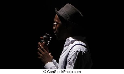 Man young in half of the turnover standing at the microphone professionally singing in a recording studio. Black background. Close up