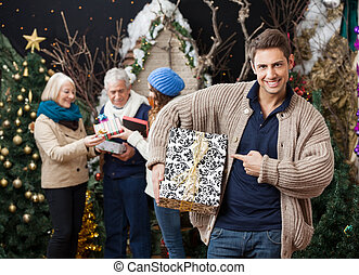 man, zeigt, an, weihnachtsgeschenk, mit, familie hintergrund