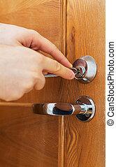 Man's hand opening door with lock picker.