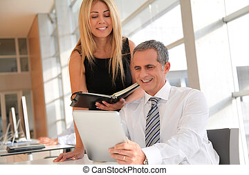 Manager and assistant working in the office
