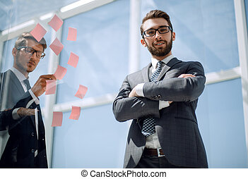 Manager and employee standing near a transparent Board in the office