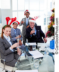 Manager and his team toasting with Champagne at a Christmas party in the office
