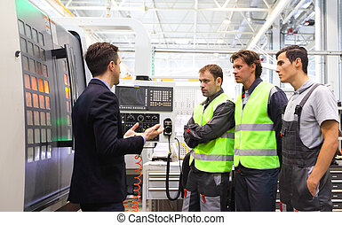 Manager and workers near CNC machines