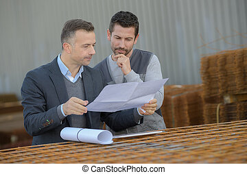 manager approving employee work at factory