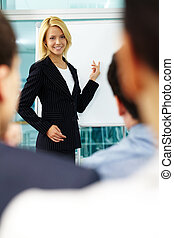 A woman manager pointing at whiteboard with colleagues listening to her