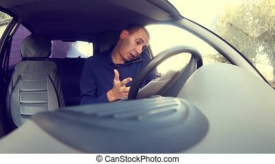 Manager businessman man driving car and talking on a mobile phone starts the car