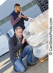 manager checking a shipping on wooden pallets