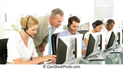 Manager checking in on call centre employees at the office