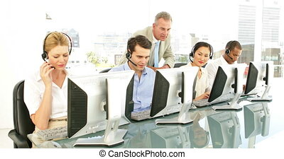 Manager checking on call centre agents at the office