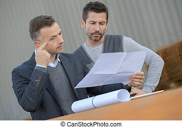 manager checking the inventory with warehouse worker