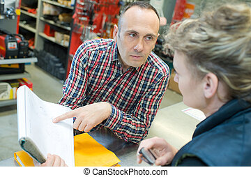 manager checks books with co-worker in a warehouse