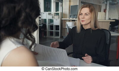 Manager discussing contract with client inside office....