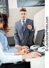 Manager Discussing With Customer Service Representatives -...