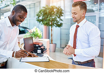 manager gives sales contract of car for signing at dealership
