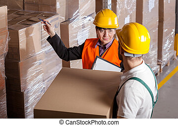 Manager giving worker instruction about loads storage in warehouse