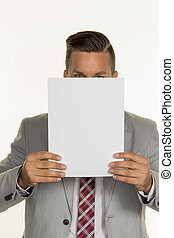 manager holding blank sheet in front of face - a young...