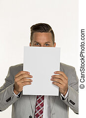 manager holds blank sheet in front of face - a young...